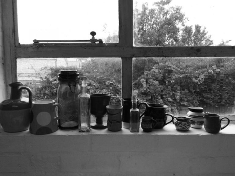 Studio windowsill with collection of jugs and containers